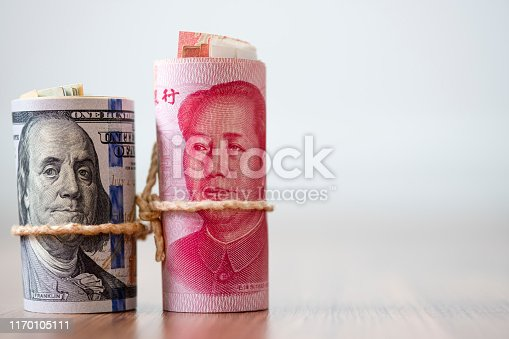 istock US dollar and Yuan banknote on wooden table. Its is symbol for tariff trade war crisis between United States of America and China which the biggest economic country in the world. 1170105111