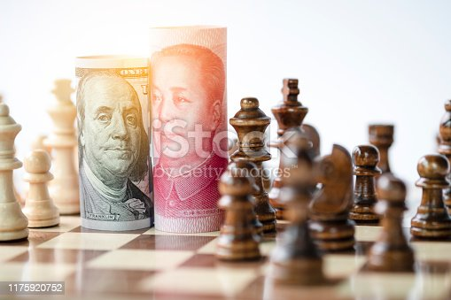 US dollar and Yuan banknote with chess for tariff trade war between United States and China which both countries battle by increase tax barrier of import and export product. Government and business.