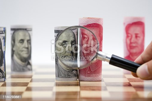istock US dollar and Yuan banknote with magnifier glass on chess board which United States and China had battle by increase tax barrier of import and export product. Government and business. 1150293881