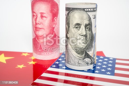 istock Dollar and Yuan currency standing on the flags of USA and China 1151360405