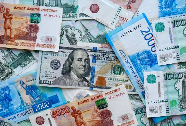 US dollar banknote on top of russian national currency, top view of mixed rouble banknotes stock photo