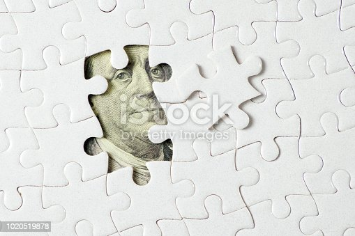 US dollar banknote hidden under white jigsaw puzzle for financial economy concept