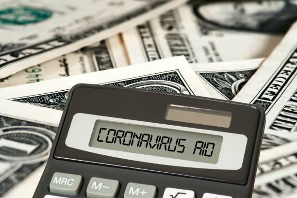Dollar banknotes, calculators and aid package Coronavirus in USA stock photo