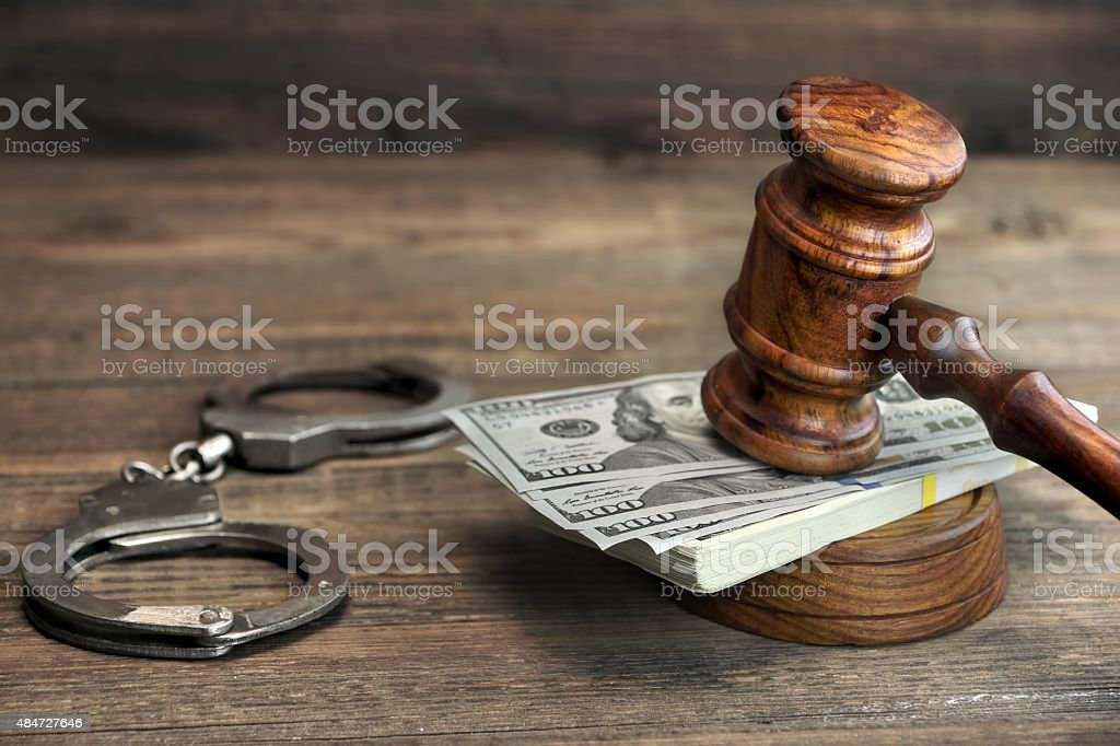 Dollar banknotes, handcuffs and judge gavel on wood table stock photo