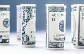 Dollar. Dollar banknotes roll in other positions. American US currency on white board and defocused background.Dollar. Dollar banknotes roll in other positions. American US currency on white board and defocused background.