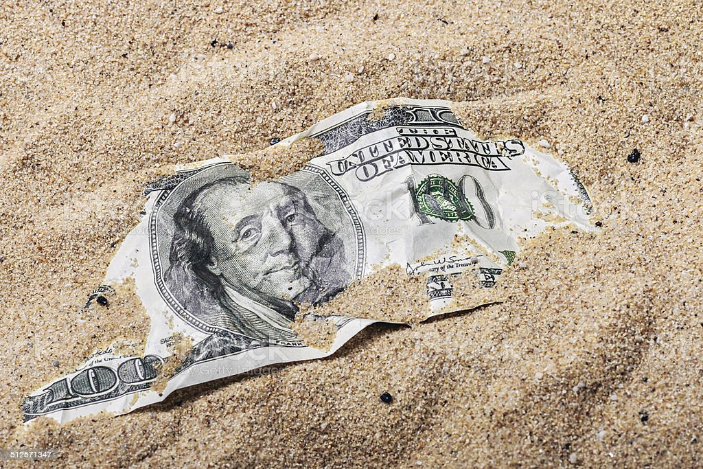 100 dollar bill buried in the sand stock photo