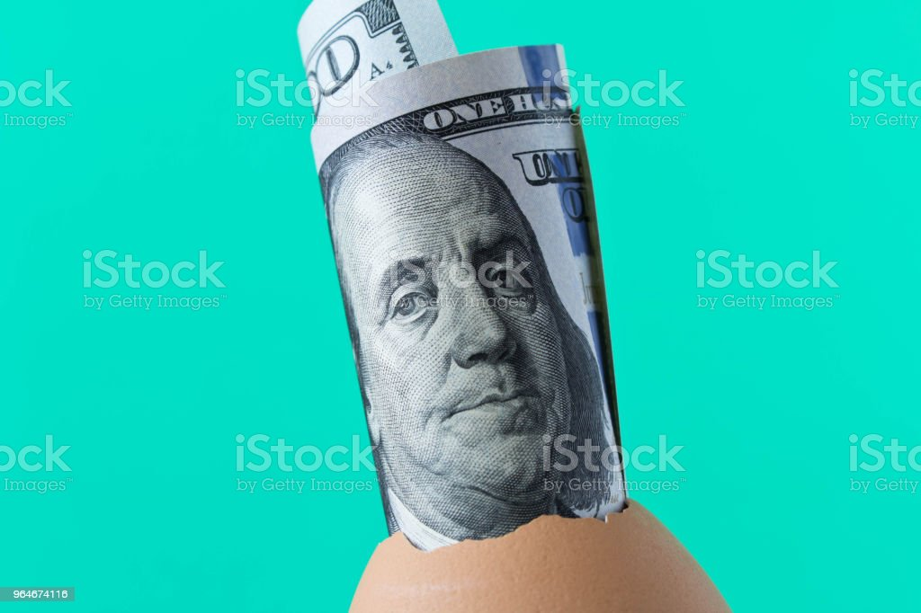 100 dollar bill in an egg shell. On a turquoise background. The concept of saving royalty-free stock photo
