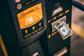 A close-up of a dollar bill inserted into a parking ticket machine in a parking garage