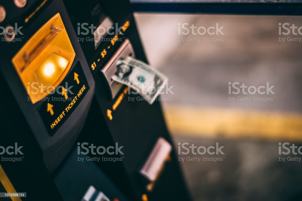 Uma nota de dólar inserida em uma máquina de bilhetes de estacionamento em uma garagem de estacionamento - foto de acervo