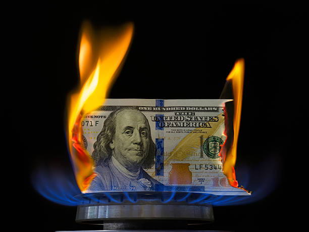 dollar bill on fire in gas burner flame. - money black background stock photos and pictures