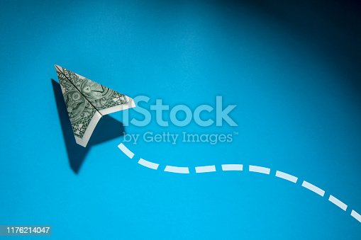 This is a photograph of United States One Dollar Bill in the shape of a paper airplane on a blue background. There is a dotted chalk line drawn in a fun path behind the plane to create a creative likable jet like trail. There is a lot ofspace for copy on the blue bakground and the path creates a nice border and frame for any text.
