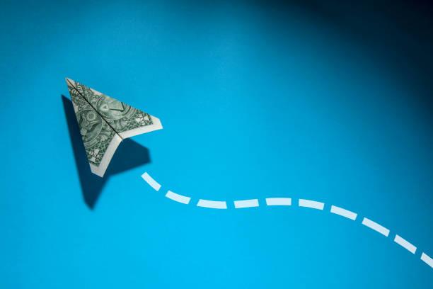 avion de papier de bill de dollar des usa avec l'idée créatrice pointée de chemin de craie sur le fond bleu - money photos et images de collection