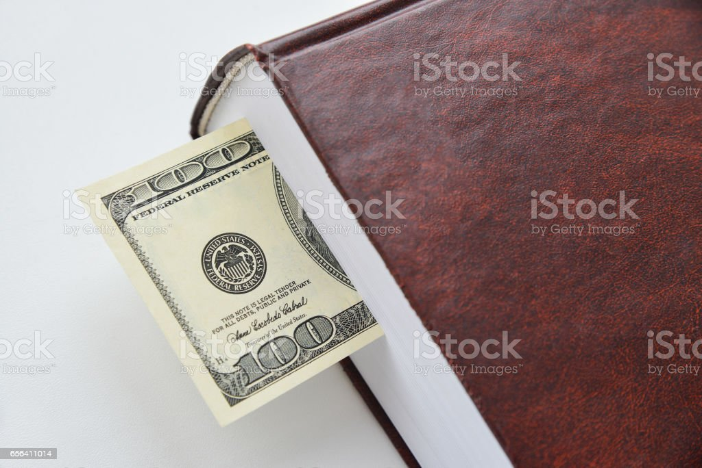 Dollar bill used as a bookmark in a book stock photo
