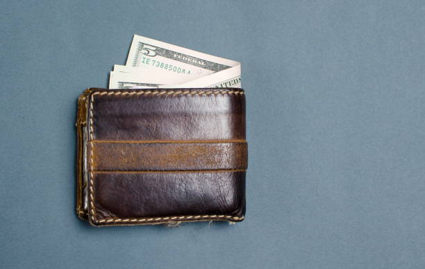 dollar bills in brown leather wallet - spending money stock photos and pictures