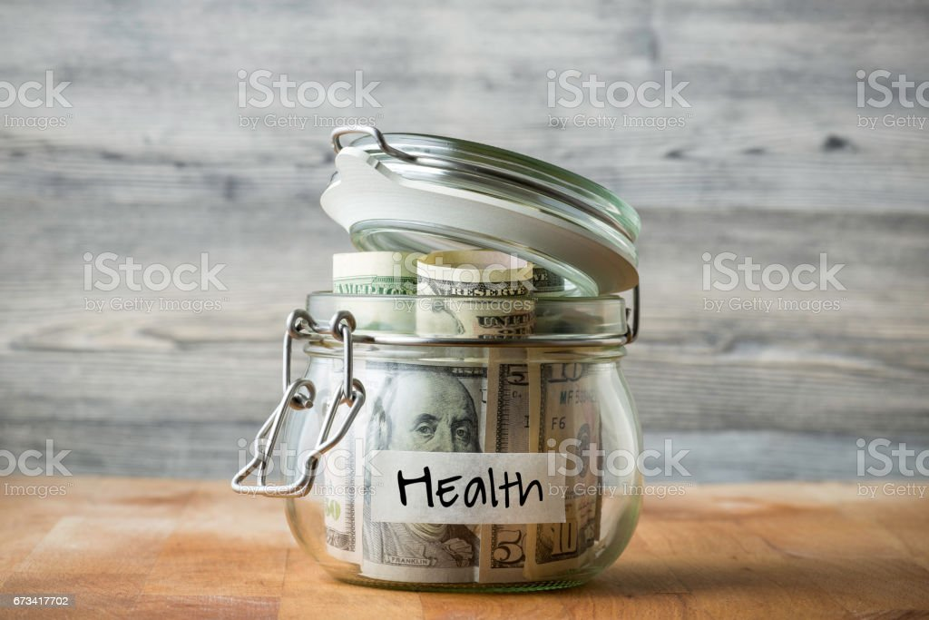 Dollar bills in glass jar isolated on wooden background. Saving money for health. stock photo