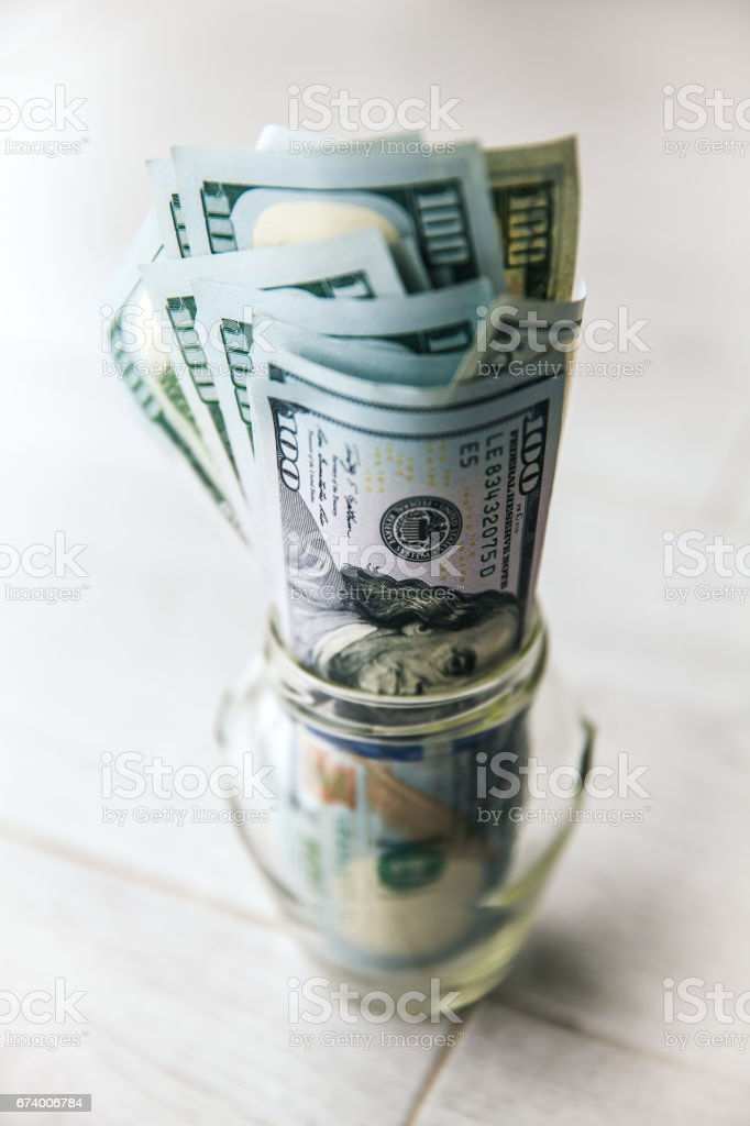 Dollar bills in glass jar on wooden background royalty-free stock photo