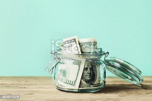 istock Dollar bills in glass jar. Saving money, economy, finance concept. 624511076