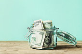 Dollar bills in glass jar. Saving money, economy, finance concept.