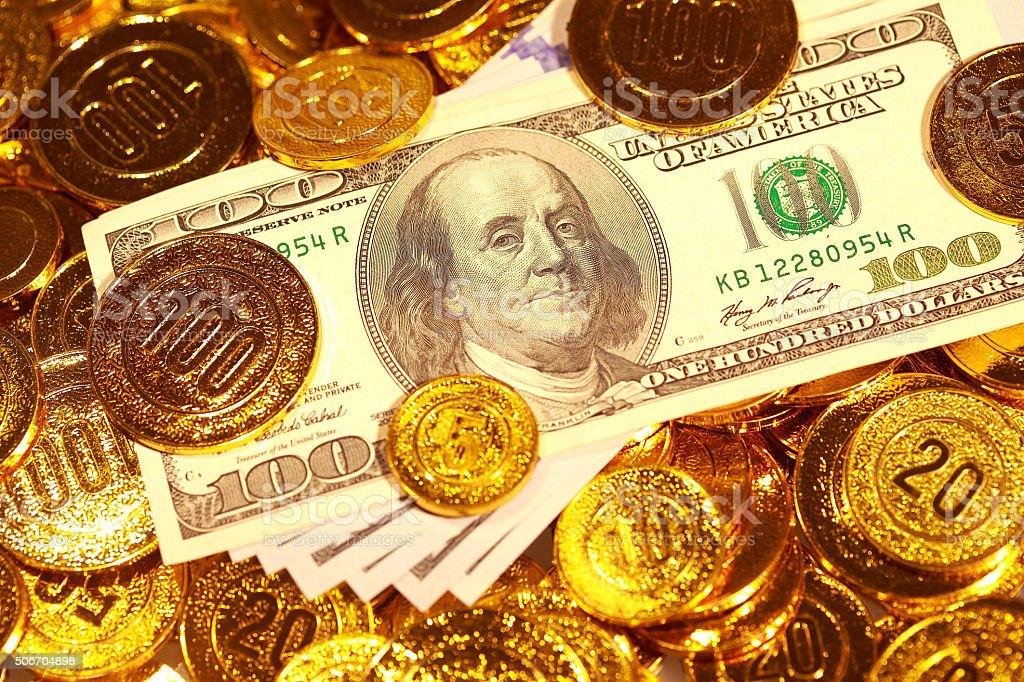 Dollar bills in Golden coins heap stock photo