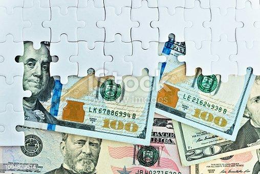 US dollar bills in jigsaw puzzle.