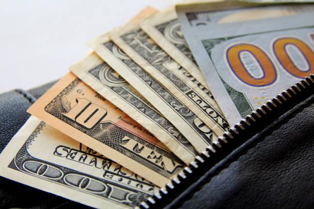 Billets d'un dollar furtivement hors de la noire en cuir sac, gros plan - Photo