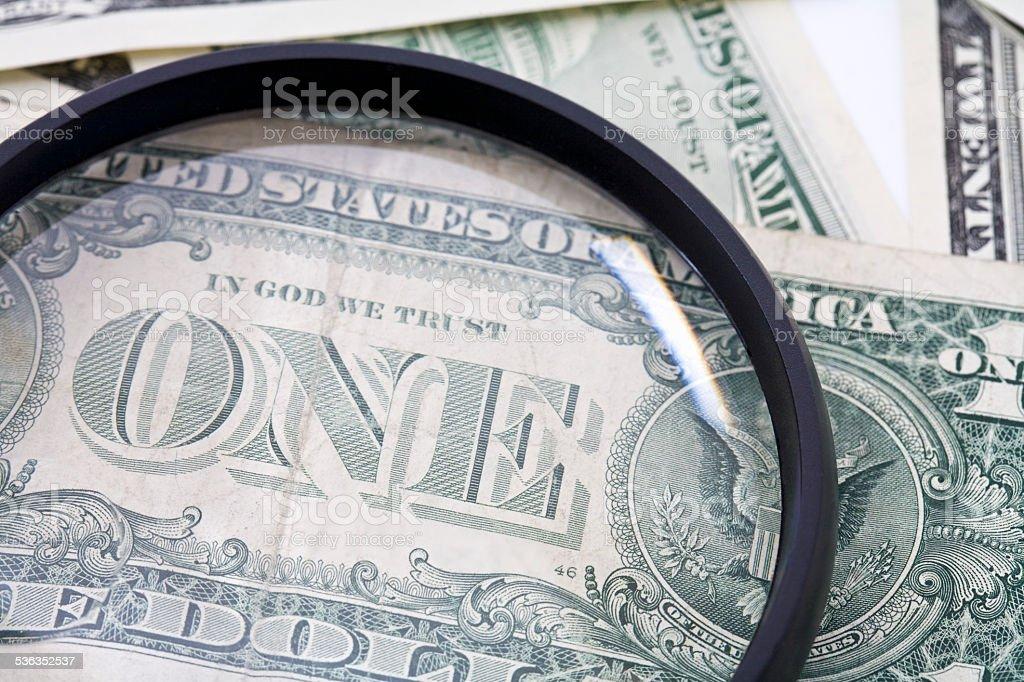 US Dollar bills seen through magnifying glass, close up stock photo