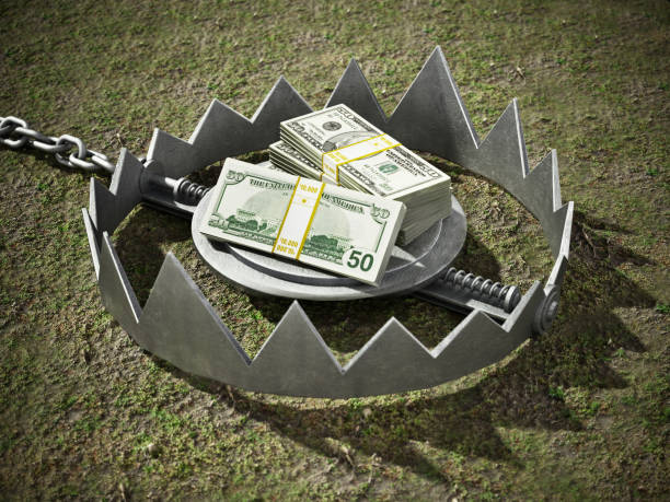 Dollar bills standing at the middle of open bear trap Dollar bills standing at the middle of open bear trap. trap stock pictures, royalty-free photos & images