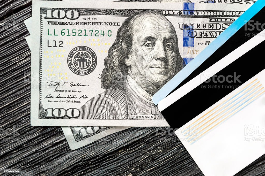 Dollar bills with plastic cards on the black wooden table stock photo