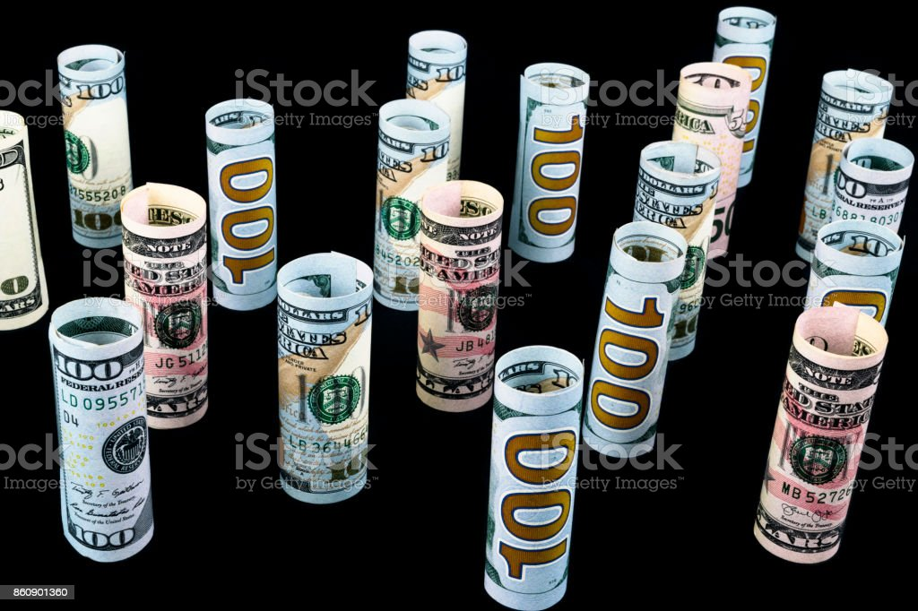 Dollar. Dollar banknotes roll in other positions. American US currency on black board. American dollar banknote rolls in all denominations isolated on black background stock photo