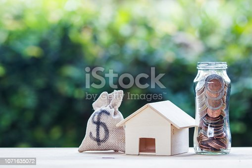istock US dollar in a money bag, small residential, house model on table against green nature background. 1071635072
