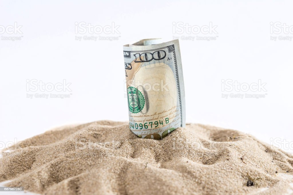 dollar in sand with shell isolated on white. summer concept stock photo