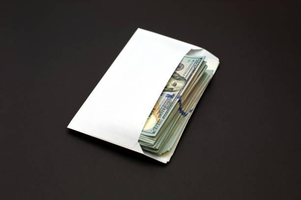 Dollar money in the envelope on black background bonus, reward, benefits concept. stock photo