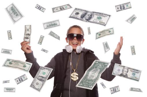 Successful hip hop style superstar under a dollar money rain. Wearing a dollar bling necklace.