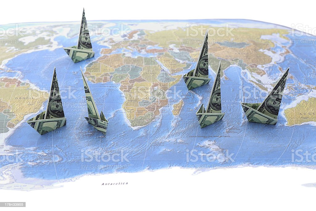 Dollar Paper Boats on World Map royalty-free stock photo
