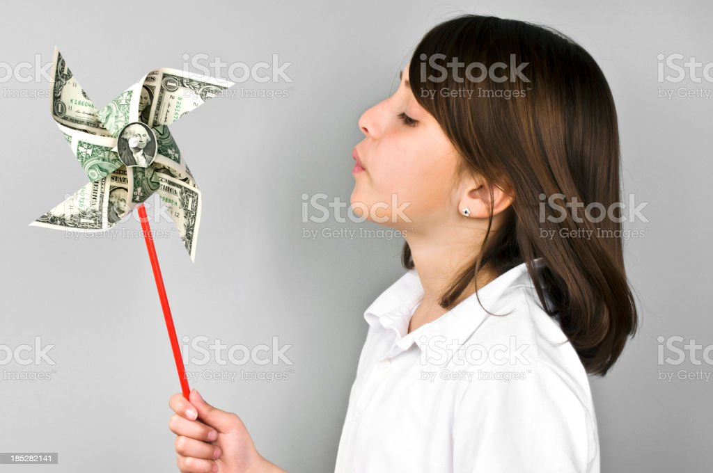 Dollar pinwheel to little cute girl royalty-free stock photo
