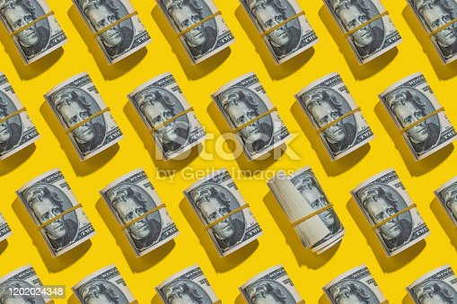 Twenty dollar notes roll repetitive flat lay on yellow background