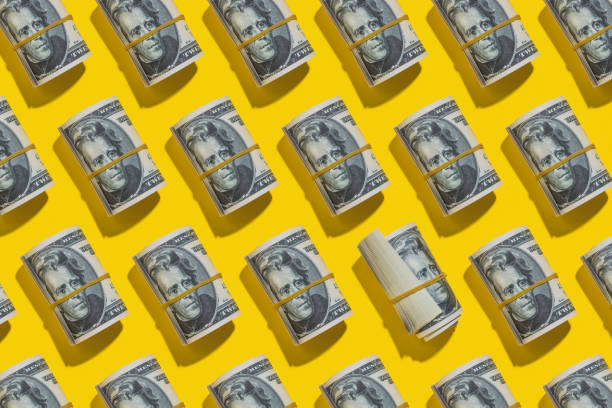 Dollar rolls flat lay on yellow background stock photo