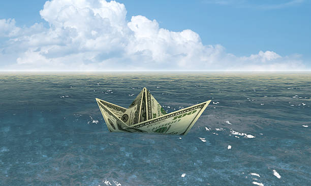 Dollar ship in water - economy concept stock photo