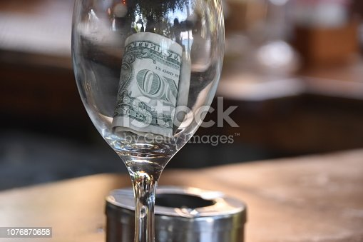 istock Dollar tip in glass cup 1076870658