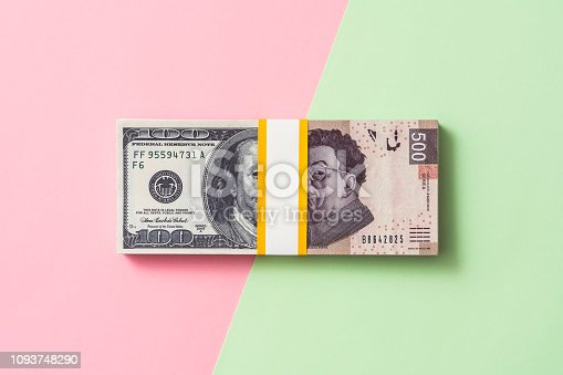 International money exchange concept. Half dollar half Mexican peso banknote on pink and green color background.