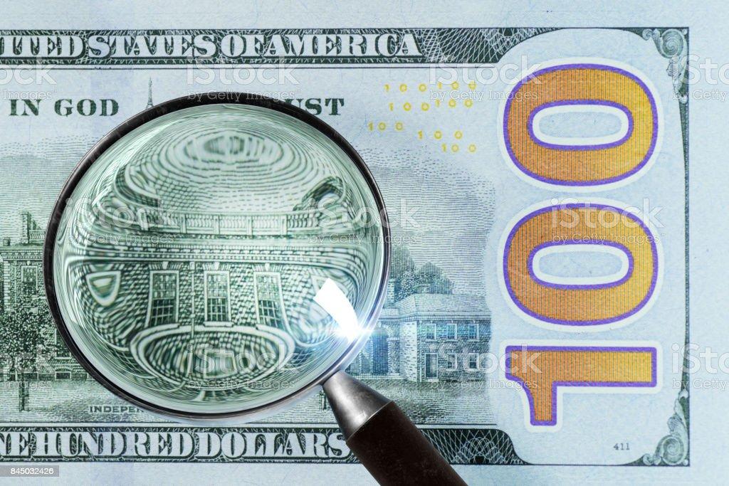 100 US Dollar under magnifying glass stock photo