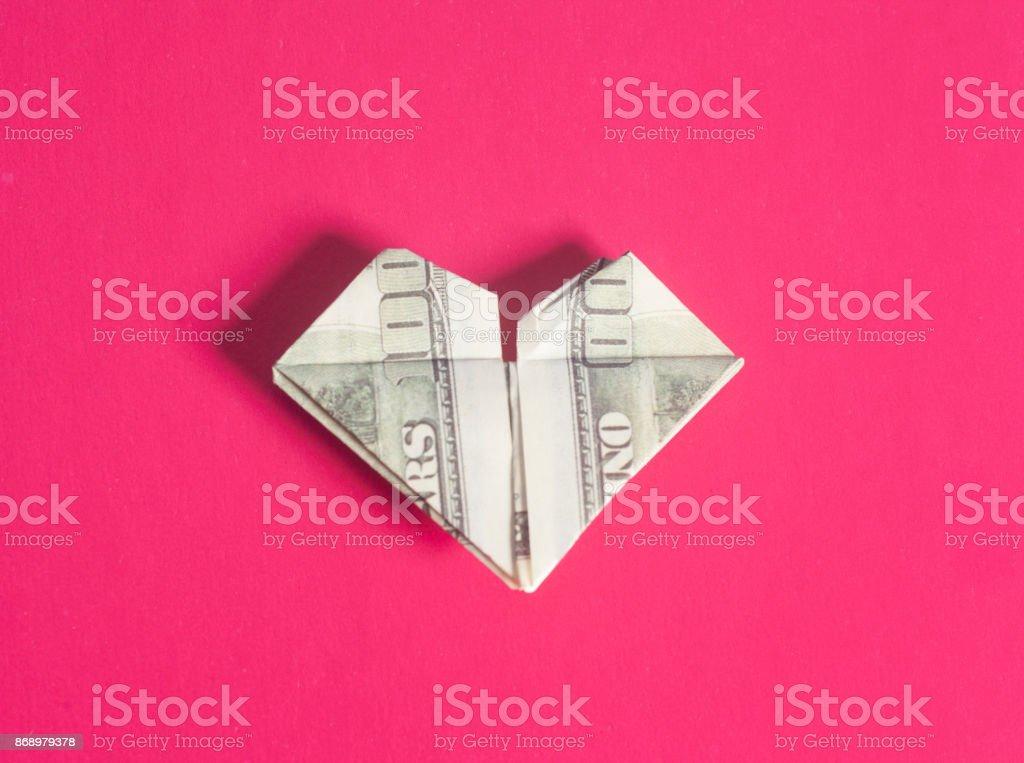 Dollar US bills in heart shape origami stock photo