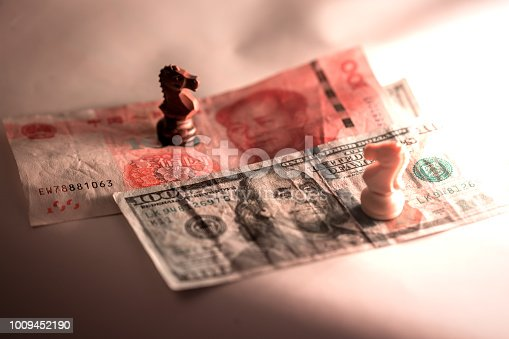 US dollar with Chinese yuan together and knight chess piece under low light