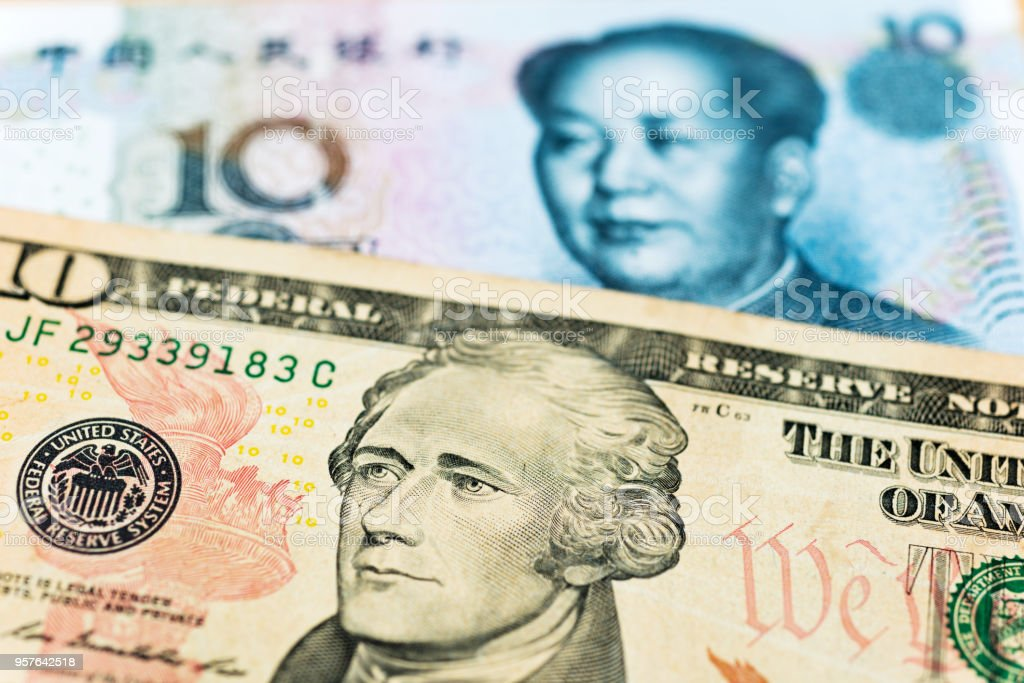 US dollars and Chinese yuan background stock photo