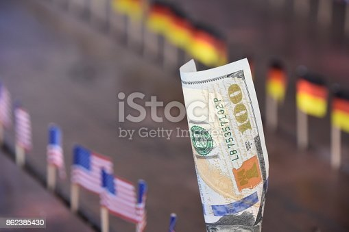 istock 100 dollars and flags of the world 862385430