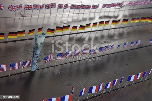 istock 100 dollars and flags of the world 862386456