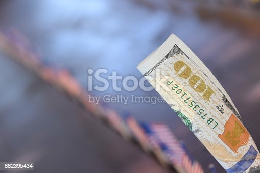 istock 100 dollars and flags of the world 862395434