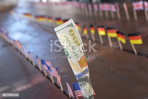 istock 100 dollars and flags of the world 862395500