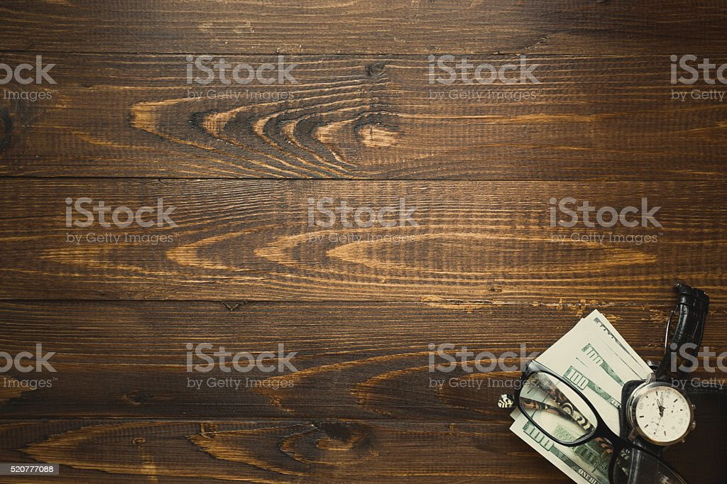 US dollars and hand watch over dark wooden background stock photo