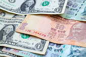 istock US Dollars and Indian Rupees banknotes 1190821660
